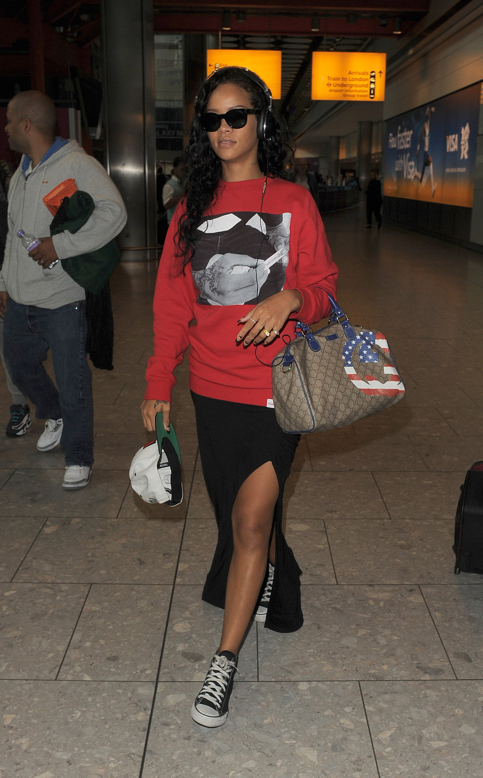 International pop star Rihanna paired her black Chuck Taylor Core Ox sneakers with a black thigh high split maxi skirt and an oversized red pullover sweater for an effortless airport look.