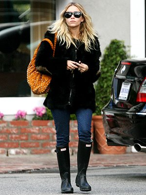 "Our darling Ashley Olsen paired her black Hunter ""Original Tall Classic"" boots with denim and an overcoat for a simple yet chic look."