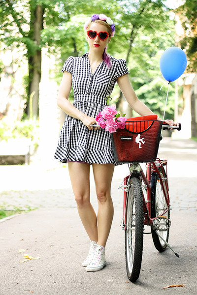 "Romanian blogger ""Skinny Buddha"" pairs classic white high top Converse sneakers with a black and white checkered mini dress and flowered headband for a cool, whimsical look."
